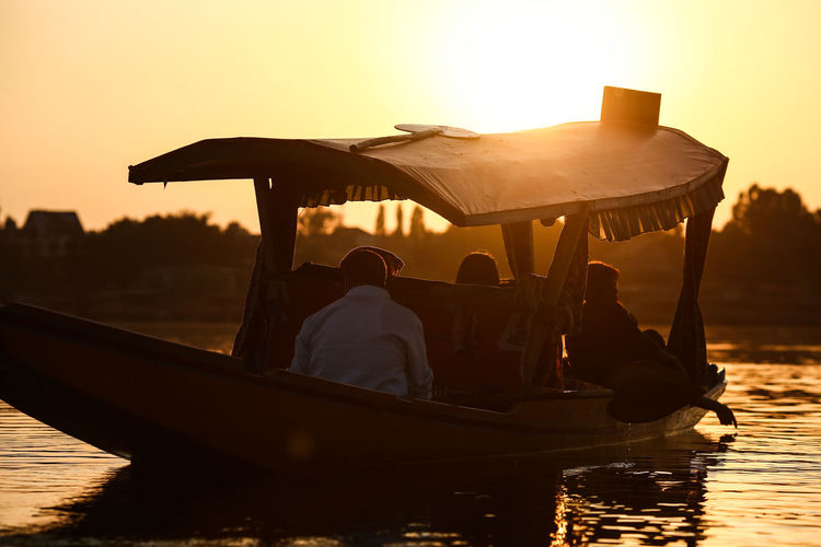 People In Boat On Lake Against Sky During Sunset