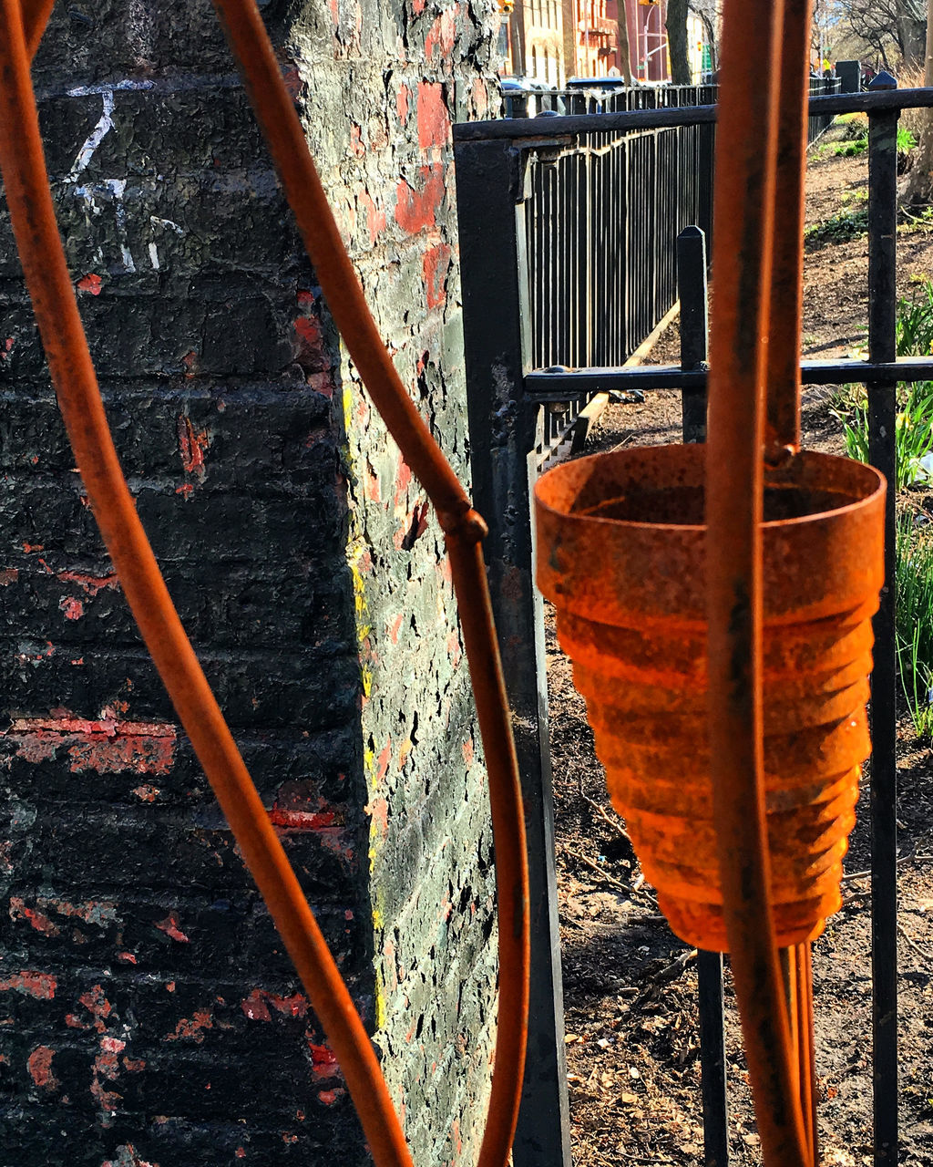 no people, metal, day, nature, orange color, rusty, outdoors, railing, architecture, close-up, plant, built structure, sunlight, wall - building feature, wood - material, focus on foreground, old, weathered, gardening equipment, front or back yard, well