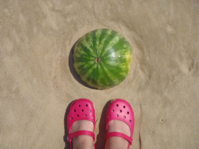 Low Section Of Girl Standing By Watermelon On Sandy Field