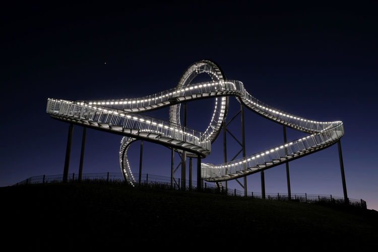 This sculpture Tiger and Turtle - Magic Mountain, by German artists Heike Mutter and Ulrich Genth, is modelled on a roller coaster. Visitors are able to walk the steps. Abstract Architecture Bridge - Man Made Structure City Cityscape Decision Decisions Ferris Wheel Illuminated Looping Night No People Outdoors Rollercoaster Sky Staircase Staircases Steps The Week Of Eyeem Travel Destinations Two Ways Up Fujifilm_xseries FUJIFILM X-T2 The Week On Eyem Investing In Quality Of Life