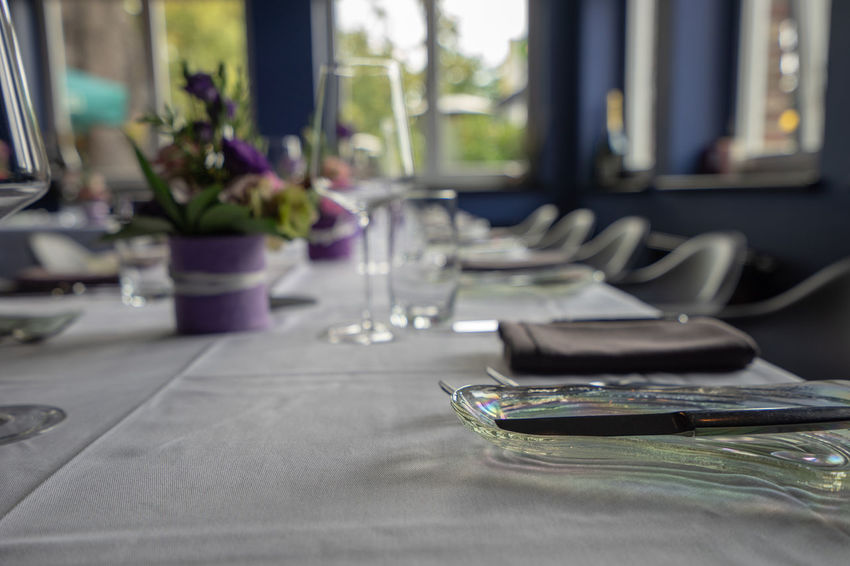 Table Glass Indoors  Glass - Material Place Setting No People Drinking Glass Plant Selective Focus Window Setting Tablecloth Household Equipment Restaurant Flower Flowering Plant Transparent Furniture Absence Day Place Mat Purple Surface Level