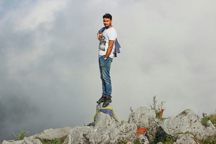 Young man standing on top of rock against cloudy sky