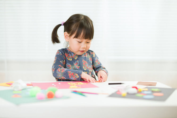 Portrait of cute girl playing on table