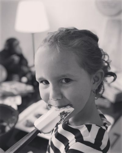 Close-up portrait of girl eating food at home