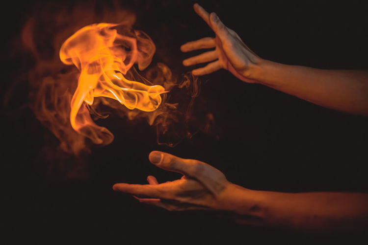 Cropped hands of person by flame against black background