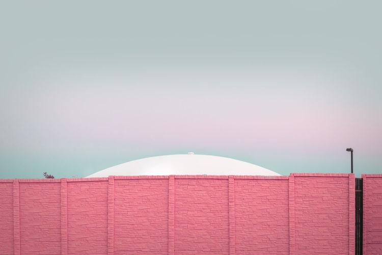 Ufo behind a pink brick wall