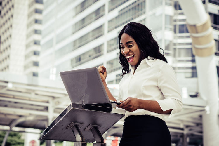 Young Woman With Clenched Fist Looking In Laptop While Standing Against Office Building