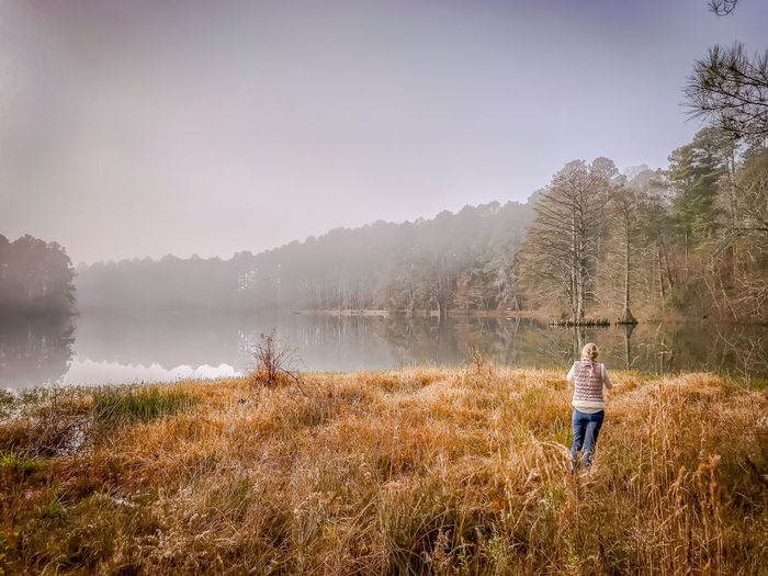 Man standing on field by lake against sky