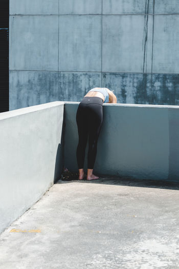 Rear view of woman standing by swimming pool