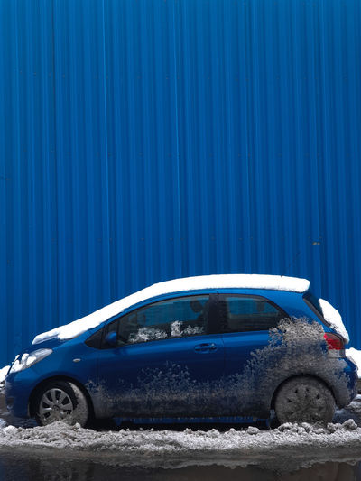 Blue car parked against wall