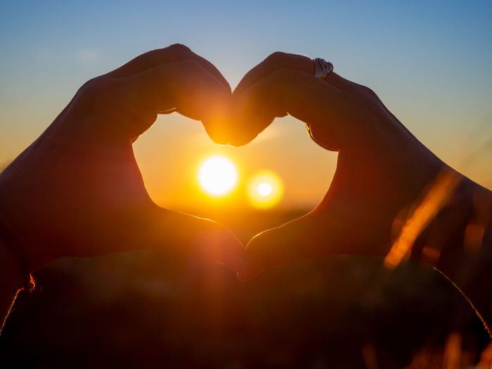 Hand holding heart shape against sky during sunset