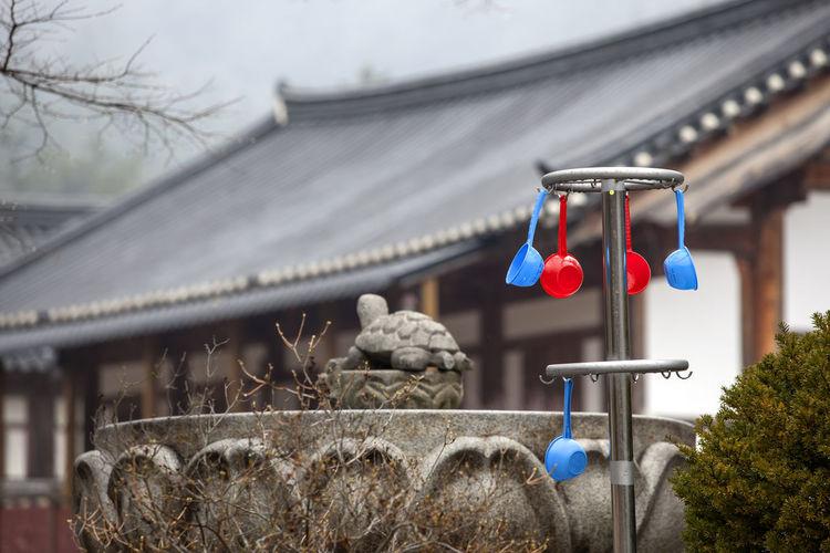 Plastic ladles hanging against house