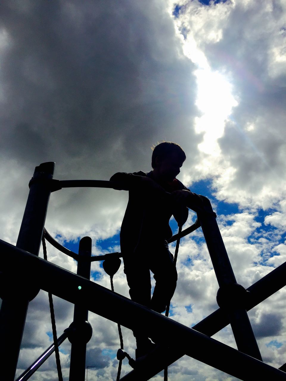 Low Angle View Of Boy On Jungle Gym Against Cloudy Sky At Playground