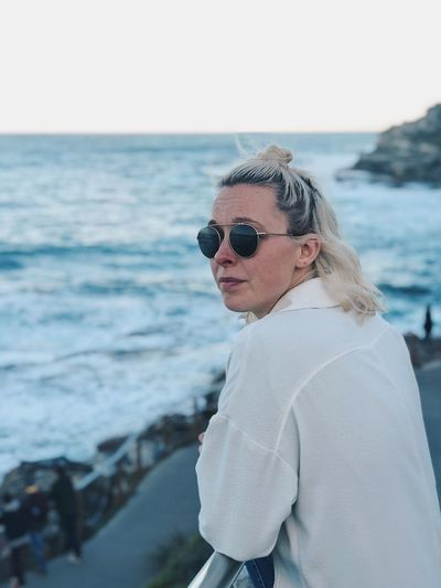 Portrait of woman wearing sunglasses while standing by sea against sky