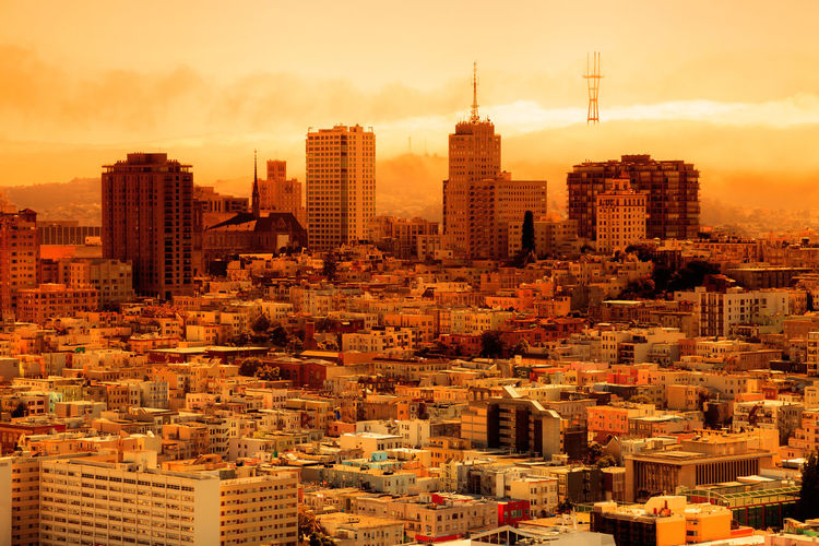 Aerial view of buildings in city against sky during sunset