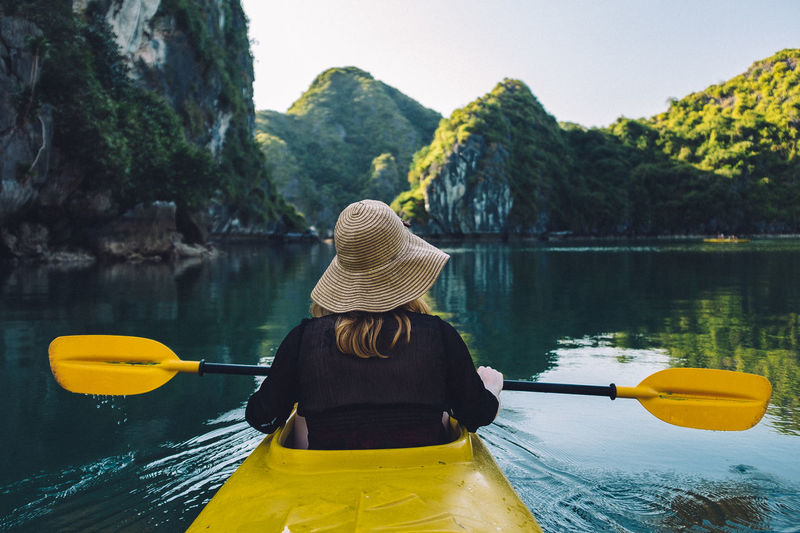 Kayaking in the Halong Bay in Northern Vietnam. Be. Ready. Halong Bay  Vietnam Adventure Beauty In Nature Day Hat Kayak Leisure Activity Life Jacket Lifestyles Nature Nautical Vessel Oar One Person Outdoors Real People Rear View Rowing Scenics Sitting Transportation Water Women Yellow