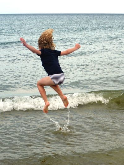 Lebensfreude I Like To Be At The Seaside Girl Playing On The Beach Jumping For Joy Lebensfreude Sea Water Horizon Over Water Fun Jumping Motion One Person Happiness Mid-air Enjoyment Outdoors Beach Rear View