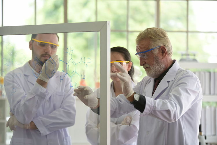 Scientist discussing formula while standing in laboratory