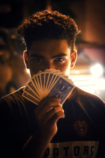 Close-up portrait of young man holding playing cards at night