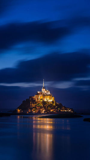 Illuminated mont saint michel with reflection in sea against sky