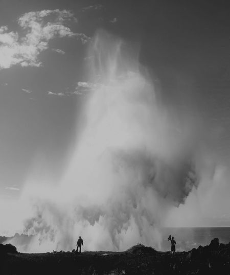 People Standing On Splashing Sea Waves