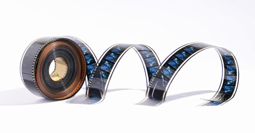 Coil of movie film with a section of the film unrolled showing the individual frames on a white background Film MOVIE Photographic Memory Retro Roll Cinematographic Ciné Coil Entertainment Exposures Film Industry Film Photography Frames Photography Shootermag Spool