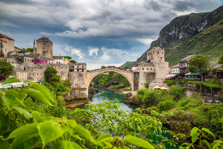 Arch bridge over river amidst buildings against cloudy sky