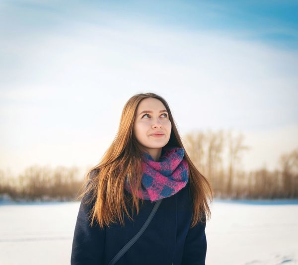 Thoughtful young woman standing outdoors during winter