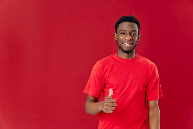Portrait of a smiling young man against red background