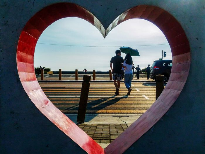 Couple crossing the pedestrian while framed by a heart.