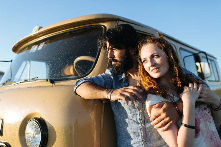Thoughtful Couple Looking Away While Leaning Against Vehicle