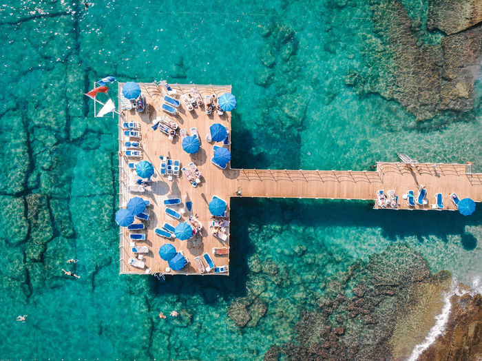 Drone View Of Lounge Chairs And Parasols On Pier Over Sea