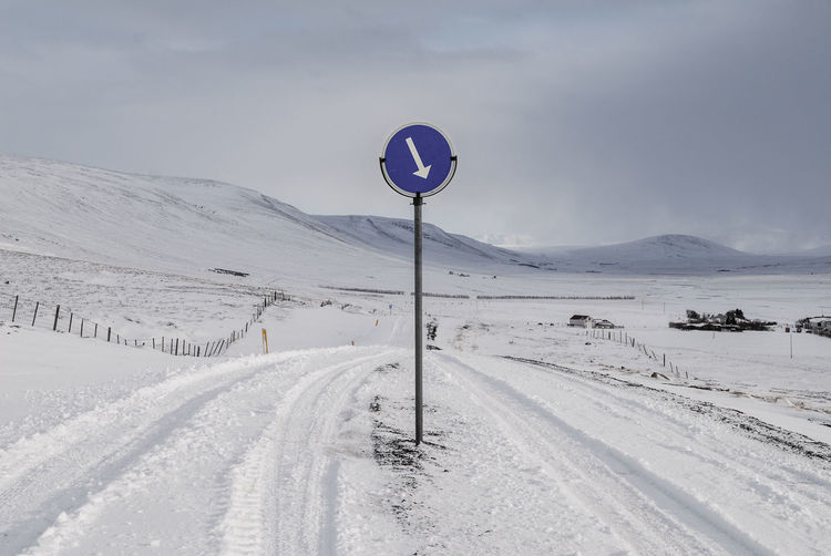 Road sign on snow covered landscape against sky