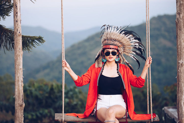 Portrait of young woman wearing headdress while sitting on swing against mountains