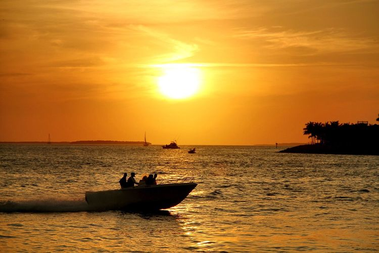 Silhouette speedboat in water against cloudy sky at sunset