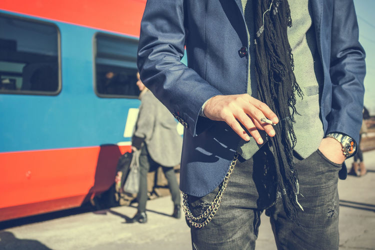 Midsection Of Man Holding Cigarette At Railroad Station Platform