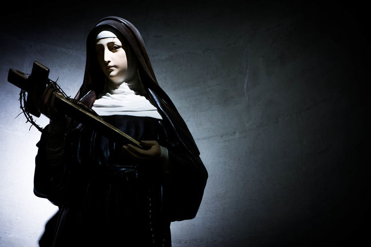 Female saint statue holding the cross against clear sky