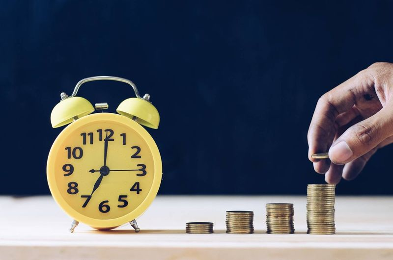 Cropped hand stacking coins by alarm clock on table