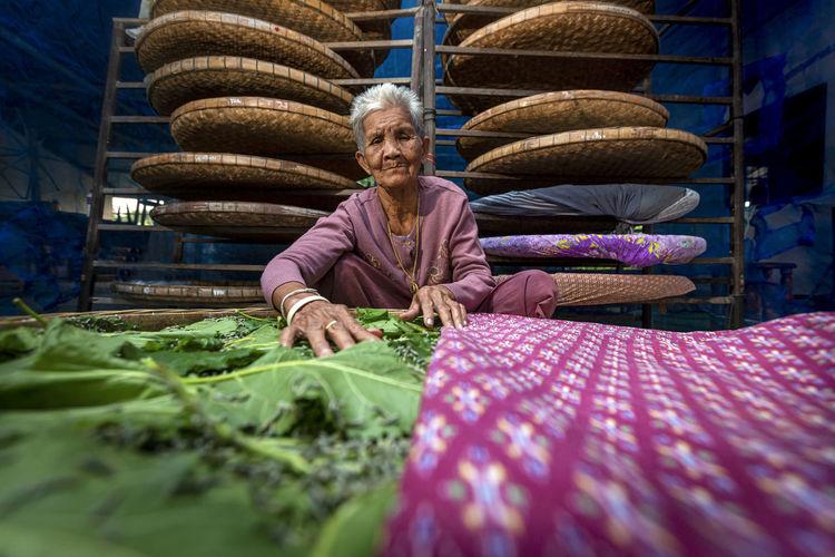 Senior woman with vegetables in wicker basket