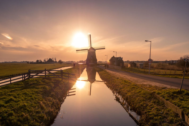 Traditional Windmill By Canal Against Sky During Sunset