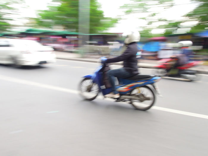 Blurred motion of people riding motorcycle on city street
