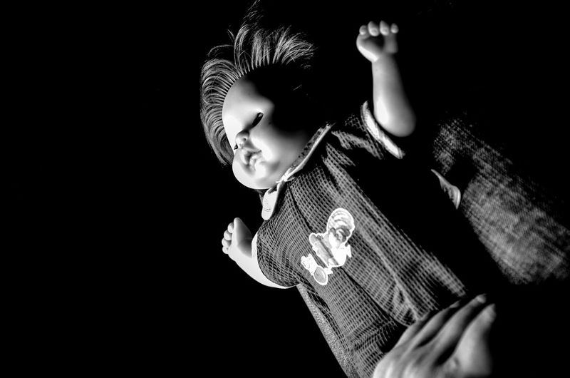 Midsection Of Person Holding Doll Against Black Background