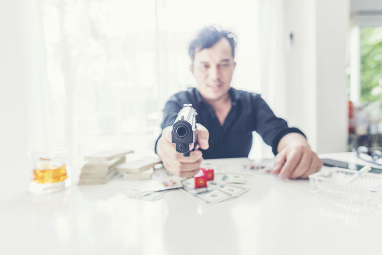 Man aiming gun while sitting with currency at table