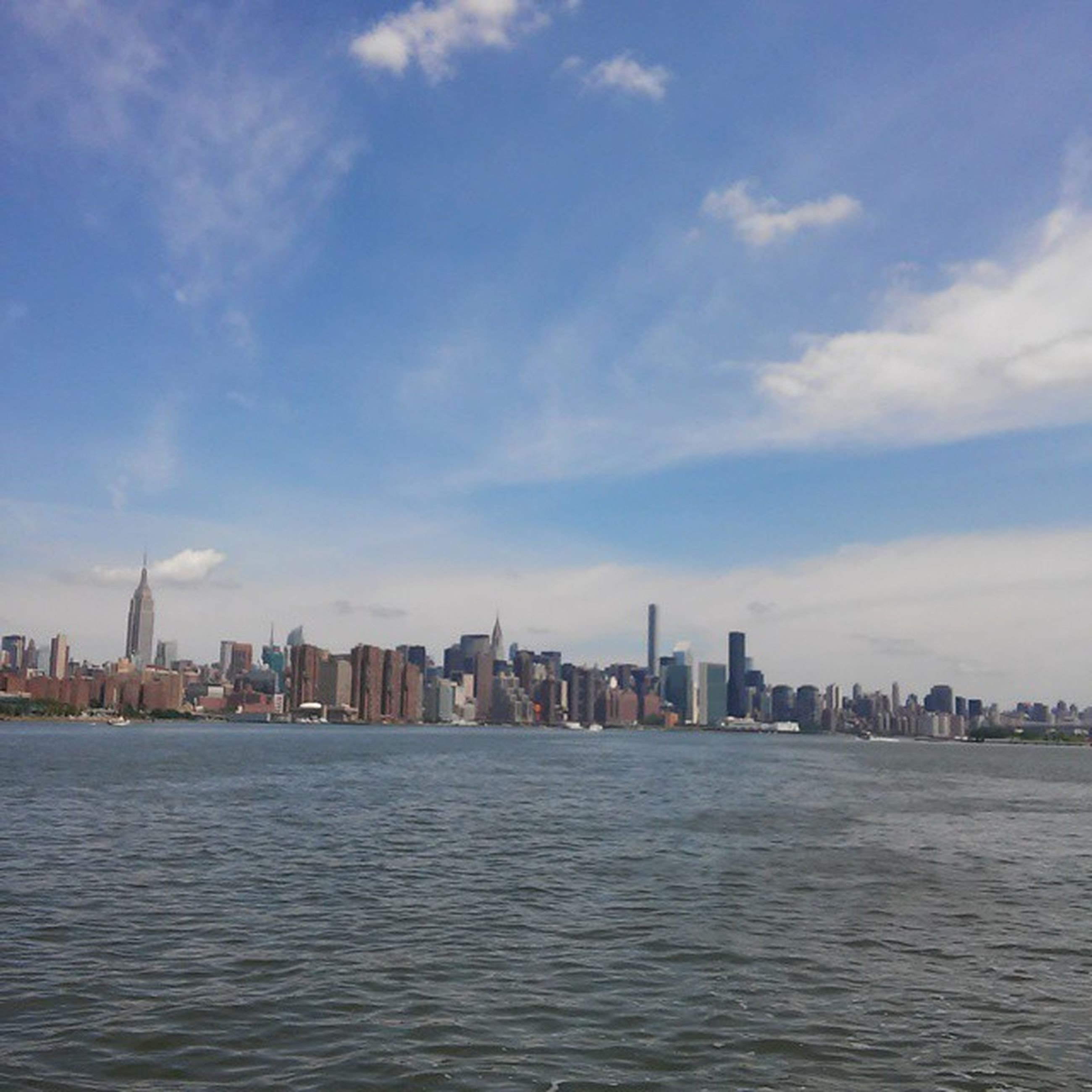 waterfront, water, building exterior, city, architecture, built structure, cityscape, sky, sea, skyscraper, urban skyline, river, blue, cloud, skyline, cloud - sky, rippled, tower, tall - high, office building