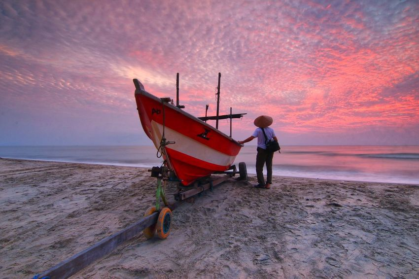 A fisherman near boat with the nice sunrise Sunrise Morning Sky Seascape One Man Only Morning Beach Dramatic Sky Sea Fisherman Boat Nautical Vessel Full Length Sunset Water Red Fishing Boat Tide