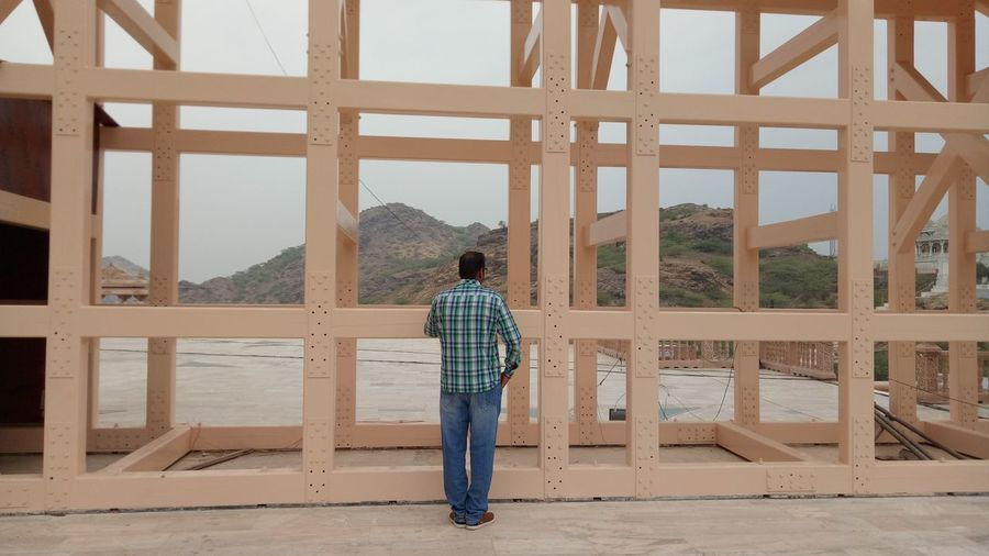 Rear view of man standing against built structure