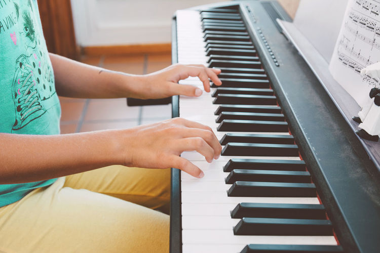 9-year-old girl playing the electric piano in front of the score book Classic Learning Music Sitting Woman Child Childhood Cute Education Female Finger Girl Key Kid Little Musical Instrument One Person People Pianist Piano Play School Sheet Music