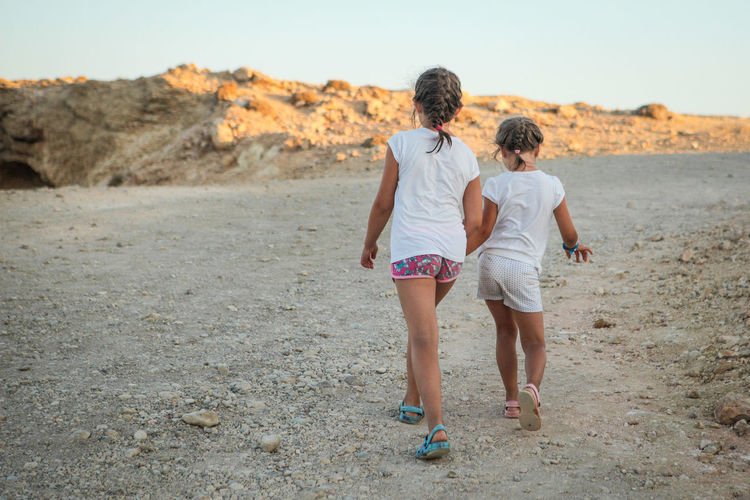 Two girls walking from the beach on a dirt road Two People Bonding Rear View Full Length Togetherness Casual Clothing Real People Emotion Love Leisure Activity Positive Emotion Land Lifestyles Women Nature Day People Walking Family Couple - Relationship Outdoors Arm Around Rock Dirt Road Copy Space