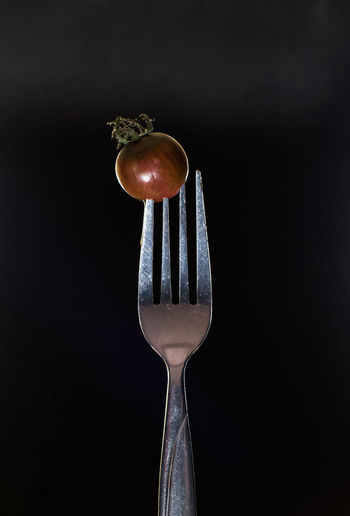 Small kumato tomato on fork isolated on the black background. Black Background Close-up Day Decor Food Food And Drink Fork Freshness Healthy Eating Indoors  Kitchen Utensil Kitchen Utensils Kumato Tomato No People Photo For Kitchen Interior Ready-to-eat Restaurant Decor Restaurant Interior Design Studio Shot Table Tomato Vegetable