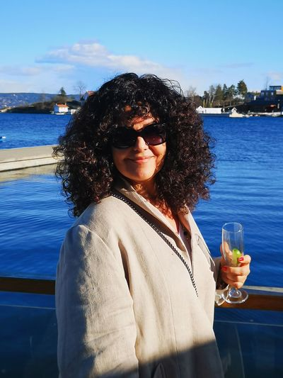 Portrait of woman with curly hair wearing sunglasses against sea in city